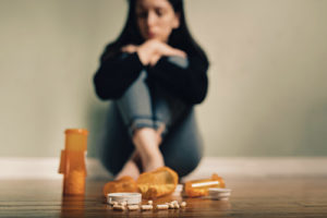 substance use disorder, woman sitting against wall in background with spilled pill bottles in the foreground